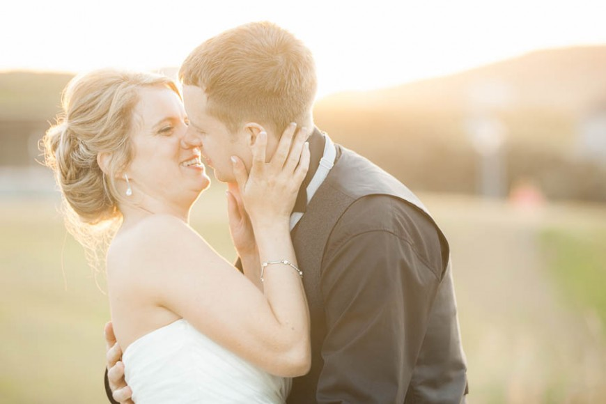 Bride and groom share an intimate moment laughing and kissing