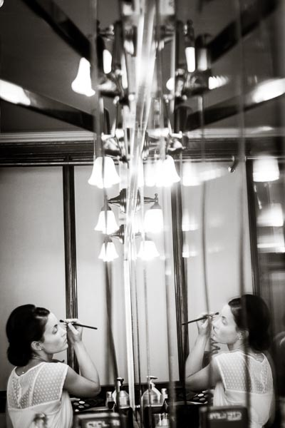 bride using eyebrow pencil while putting on her makeup