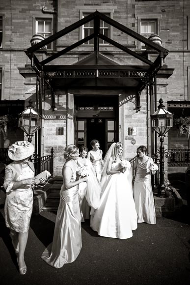 Bridal party walking outside to their wedding transportation