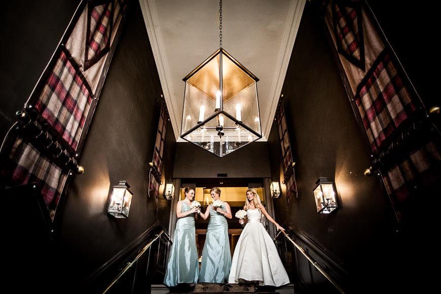 Bride and bridesmaids walking down the stairs at Dunblane Hydro