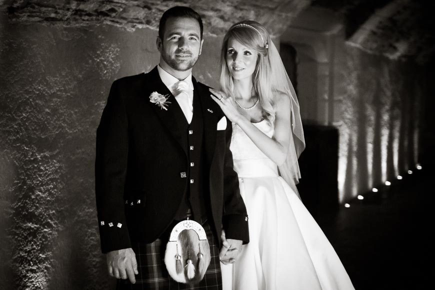 Bride and groom holding hands as the bride adoringly looks at her groom in Stirling Castle