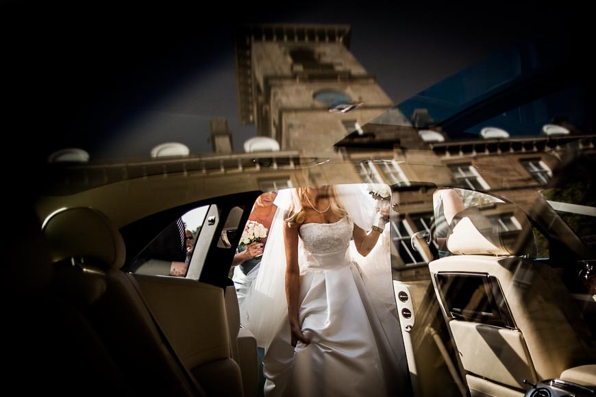 Bride gets into the car with building reflected in the glass