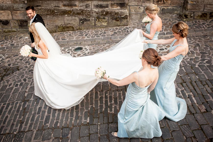 Bride gets plenty of assistance from her bridesmaids to keep her dress clean