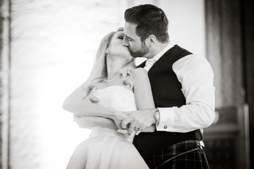 The groom dips his bride and kisses her during their first dance as a married couple
