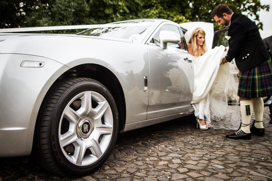 The groom helps his bride out of their Rolls Royce wedding car