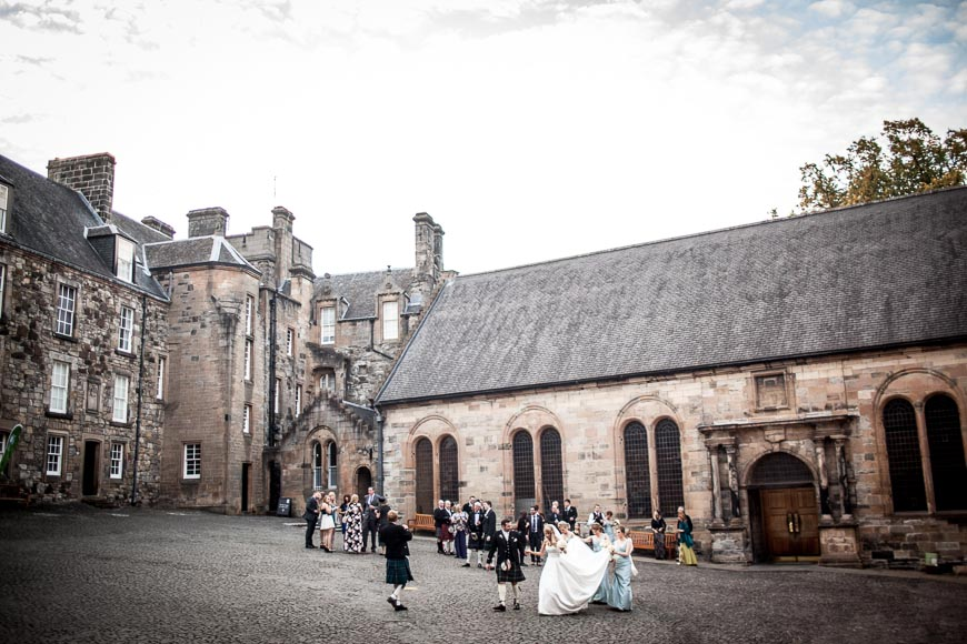 bridal party and guests walking at Stirling Castle courtyard