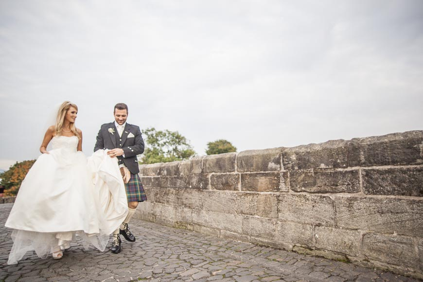 bride and groom enjoying each other walking at stirling bridge