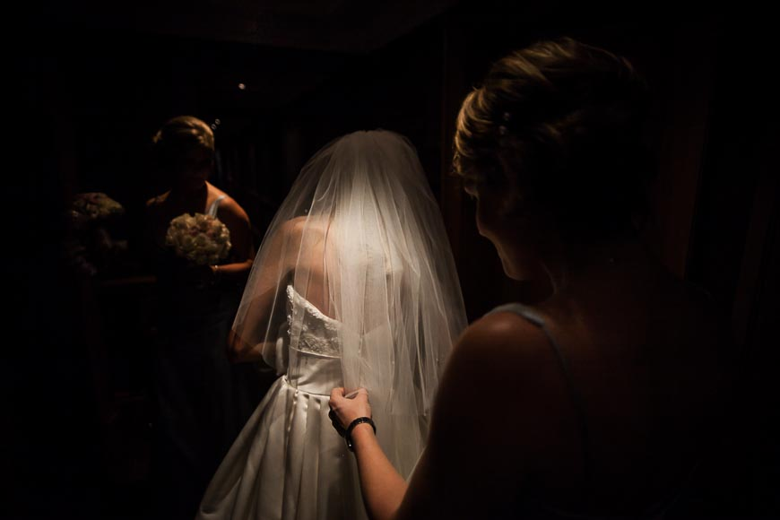 bride is dramatically illuminated by ceiling light
