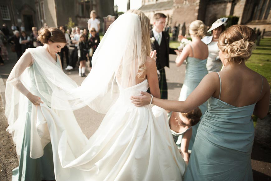 bridesmaids help the bride with her dress