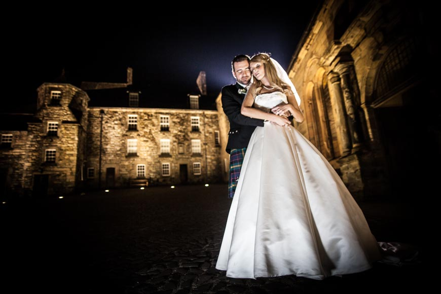 groom holding his bride outside of the Stirling Castle Courtyard