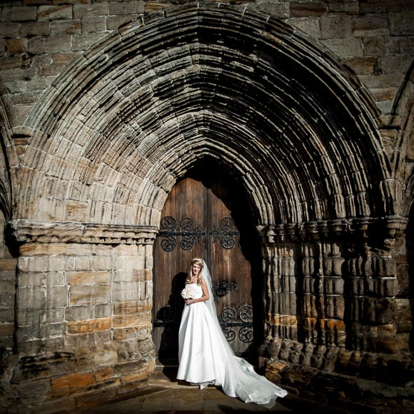 stunning bride in front of the door at Dunblane Cathedral