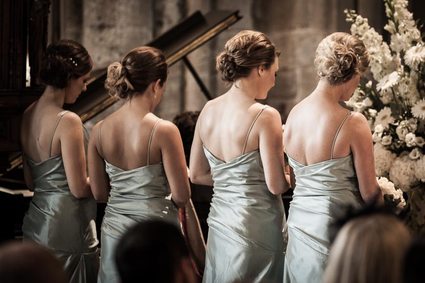 the backs of the bridesmaids in the cathedral