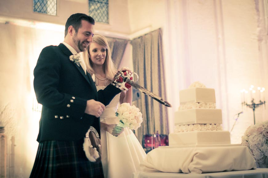 the bride and groom cut their wedding cake with a large sword