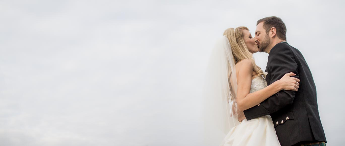 the bride and groom passionately kiss with sky as background