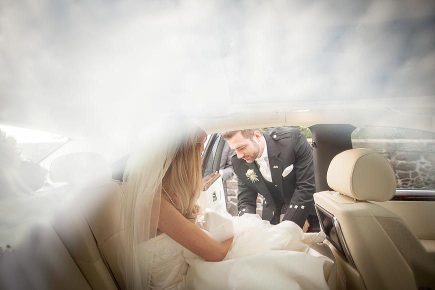 the groom gently helps his bride into their wedding car