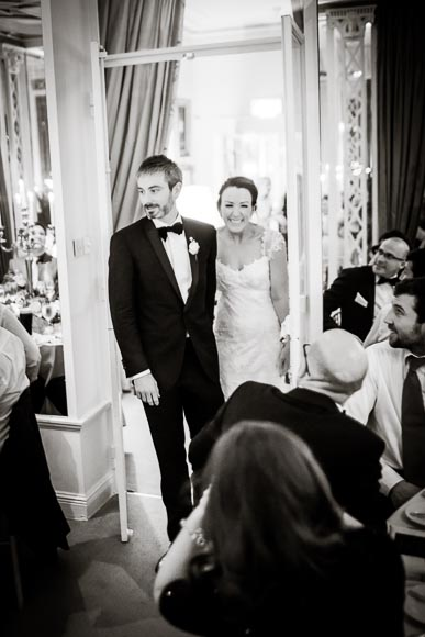 Bride & groom walking into dinner reception to their guests with large smiles on their faces