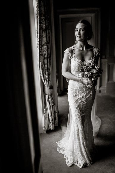 black and white full length shot of bride looking at the camera in soft window light