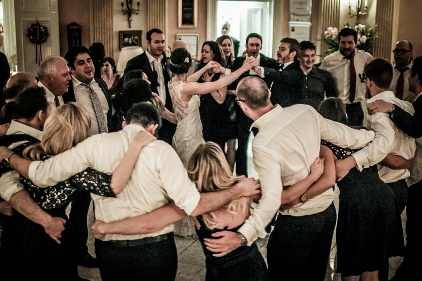 bride and groom dancing with wedding guests surrounding them during last dance of the evening
