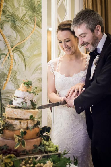 bride and groom enjoying cutting their beauitful cake made from wheels of cheese