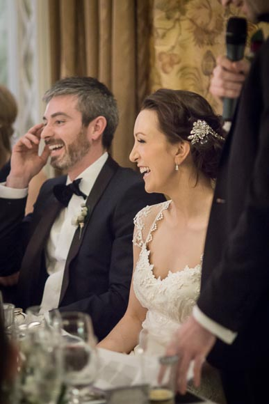 bride and groom laughing hysterically during the best mans speech