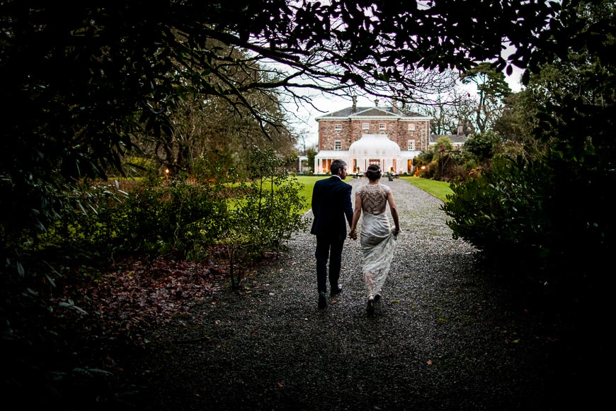 bride and groom walk back towards Marlfield House