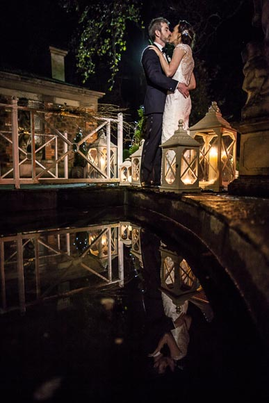 bride and grooms reflection is visible in the water as they kiss near candles