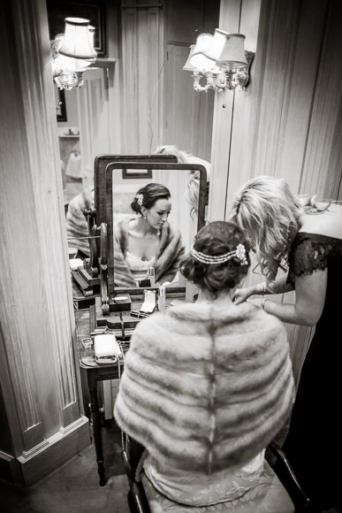 bride getting her makeup touched up before walking outside