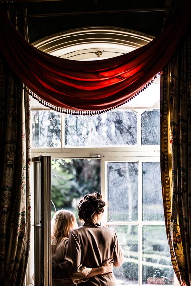 bride hugs her maid of honor in sunlight in front of window