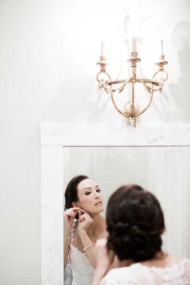 bride puts on her earing in the white marble bathroom