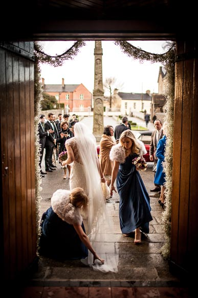 bridesmaids rush to aid the bride whose dress was caught on the ground while leaving the church in warm evening light