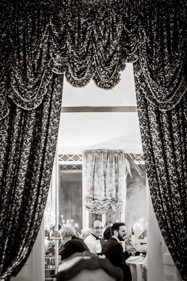 brother of the bride smiles while he is framed in by curtains