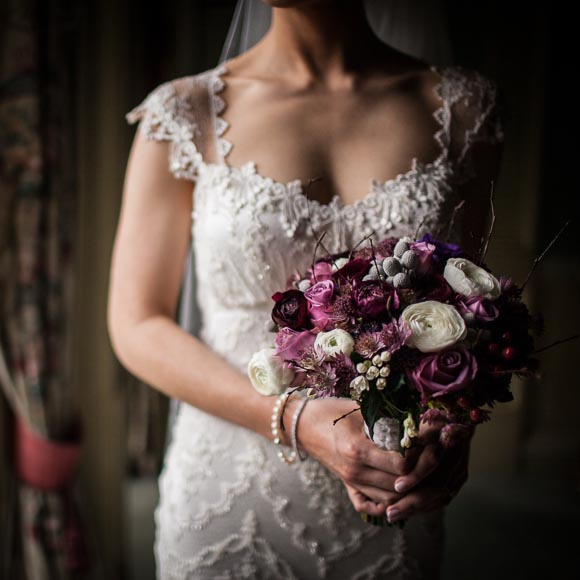 close of detail of brides boquet and dress