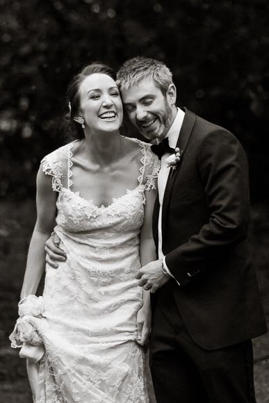 groom and bride are holding each other and laughing so hard their eyes are closed