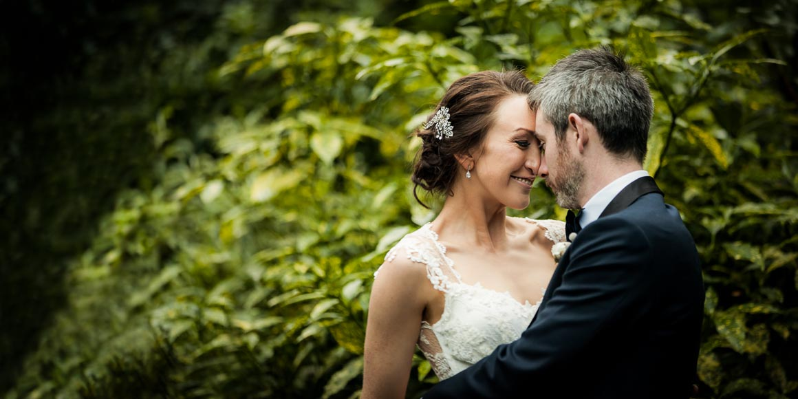 soft evening light illuminates the bride and groom cuddling in close and smiling at one another with green beautiful green bushes in the background