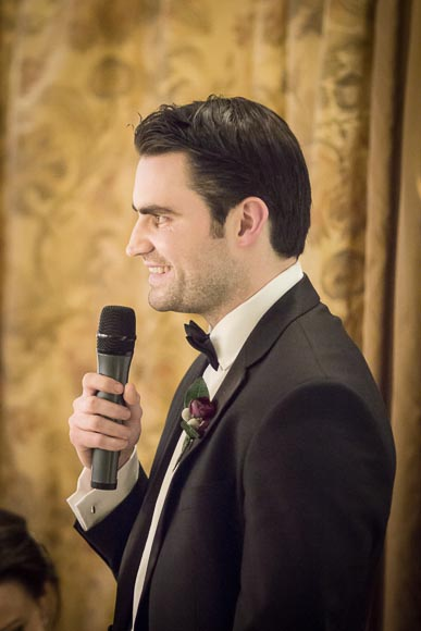 the best man smiling as he gives his speech