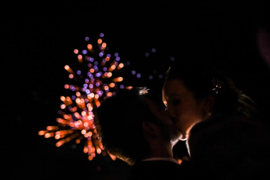 the bride and groom kissing during the fireworks on their New years eve wedding