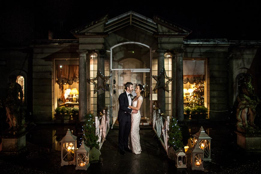 the bride and groom smile at each other in front of Marlfield House at night