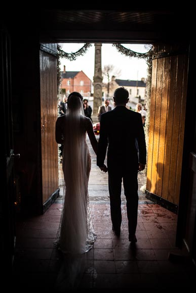 the bride and groom walk out of the church together in warm evening light