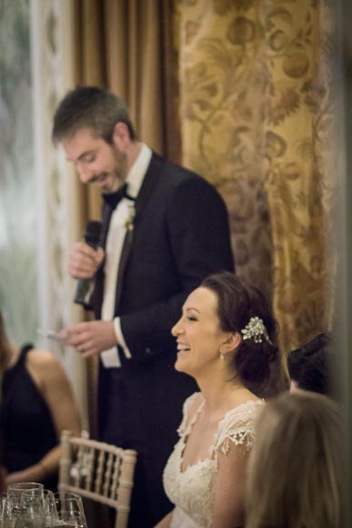 the bride laughs as her new husband gives his speech