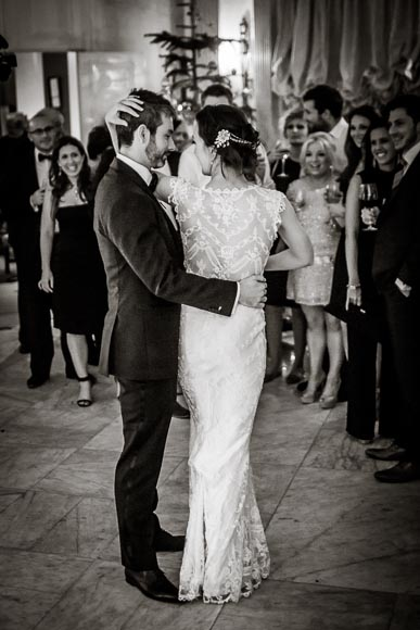 the bride wraps her arm around her groom and elegantly caresses him while they enjoy their first dance