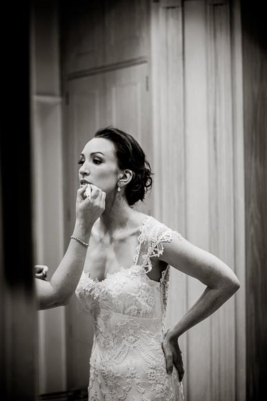 the elegant bride leans forward as she gets her lip gloss put on