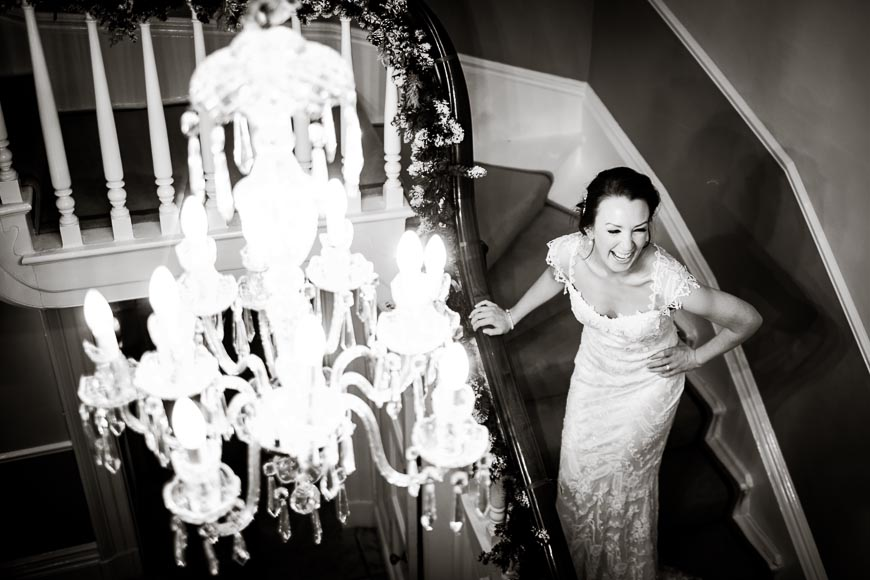 the lovely bride is laughing while standing on the staircase