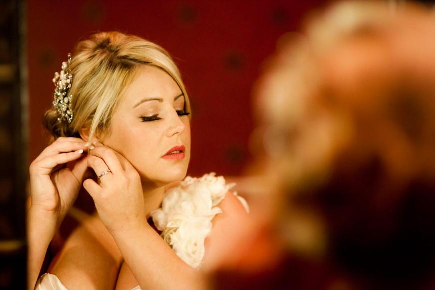 bride puts on ear rings