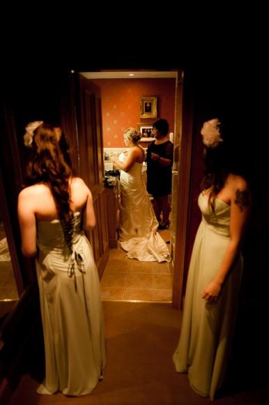 bridesmaids look on as bride gets ready