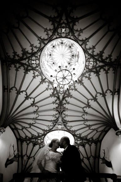 bride and groom kiss beneath ornate ceiling of dalhousie castle