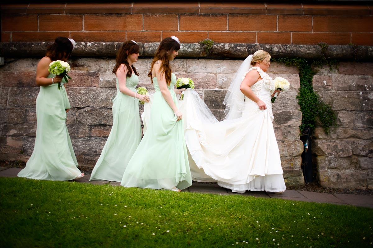 bridesmaids help bride with train on dress
