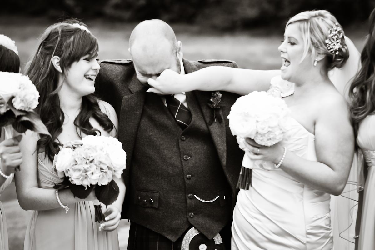 bride grabs groom's nose during wedding photos