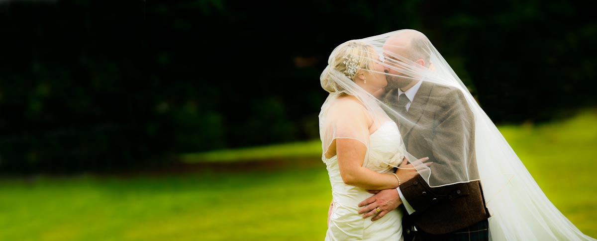 bride and groom kiss under veil on windy day