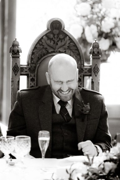 groom laughs at wedding speeches