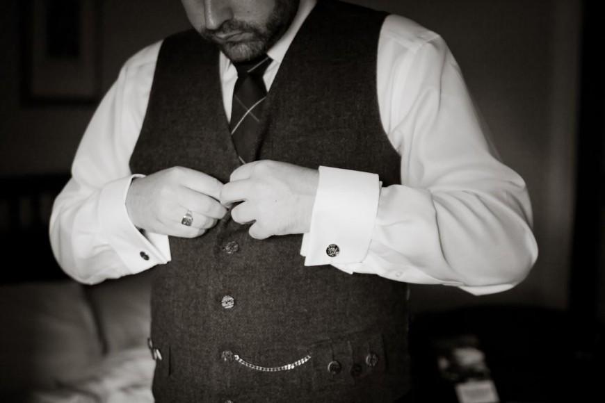 scottish groom gets ready buttoning waistcoat